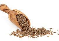 Caraway seed in an olive wood scoop and scattered over white background.