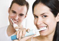 A beautiful interracial couple in the bathroom brushing teeth