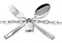 """The spoon and fork with a chain and padlock on a white background"""