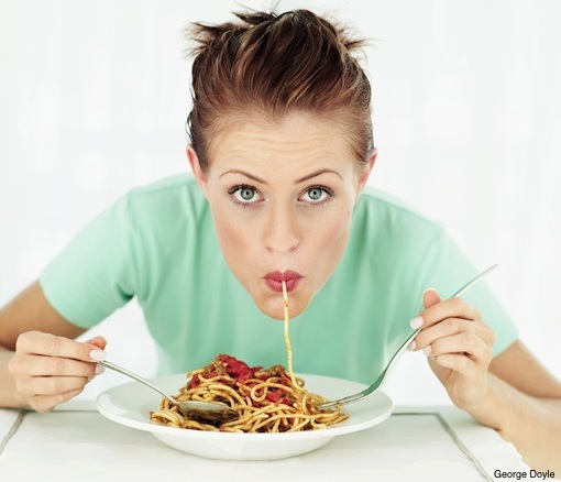 portrait of a woman eating a plate of spaghetti