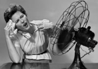 AAN3PY 1950 1950s WOMAN SITTING IN FRONT OF FAN WIPING FOREHEAD VERY HOT