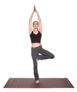 Isolated studio shot of a fit Caucasian woman holding the vrksasana Tree Pose yoga position on an exercise mat.