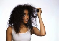 Young woman holding hair against white background --- Image by © Camarena/Image Source/Corbis