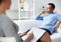 Pensive man trying to relax on sofa during psychological therapy session